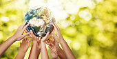 Group of children holding planet earth over defocused nature background