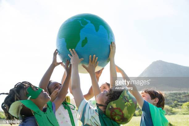 group of children holding up a large globe - environmental issues stock pictures, royalty-free photos & images