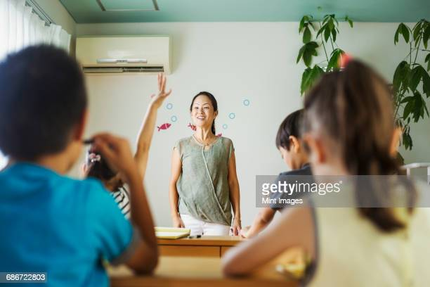 A group of children in a classroom, one with her hand up ready to answer a question.