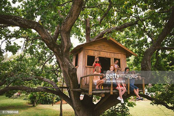 Group of children in a treehouse blowing bubbles