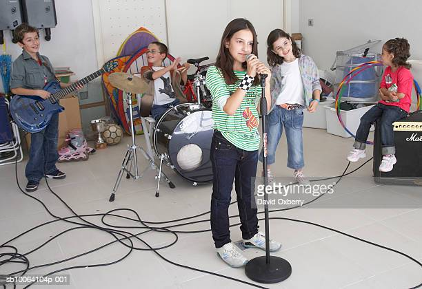 group of children (7-10) in band, playing instruments in garage - garage band stock photos and pictures