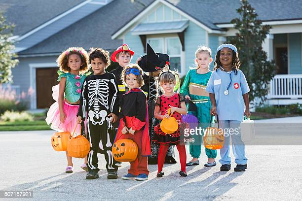 Group of children in halloween costumes in front of house