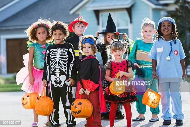 group of children in halloween costumes standing outdoors - halloween kids stock photos and pictures
