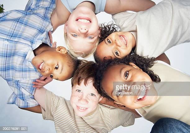 group of children (5-10) in huddle, view from below, smiling, portrait - unusual angle stock pictures, royalty-free photos & images