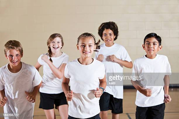 group of children in phys ed class exercising - pe teacher stock photos and pictures