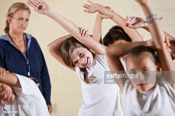 group of children in phys ed class stretching - physical education stock photos and pictures