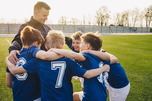 Group Of Children In Soccer Team Celebrating With Coach 1148407868