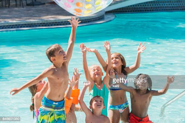 group of children in swimming pool reaching for ball - kids pool games stock pictures, royalty-free photos & images