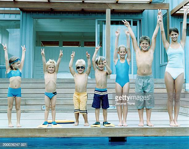Group of children (3-15) in swimwear, arms raised in victory sign