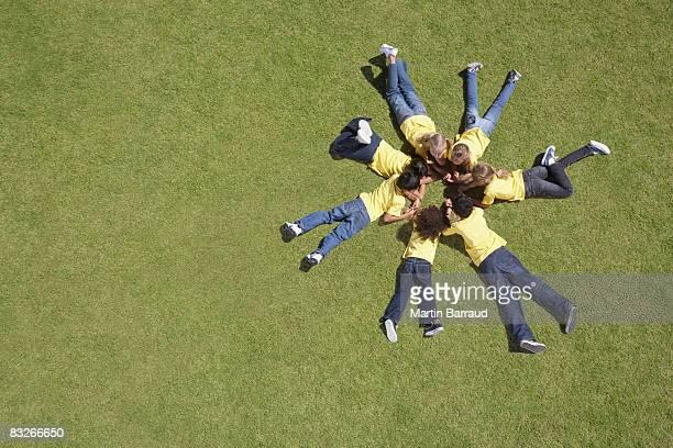 grupo de niños que descansan en hierba en un círculo alrededor de la formación - acostado boca abajo fotografías e imágenes de stock