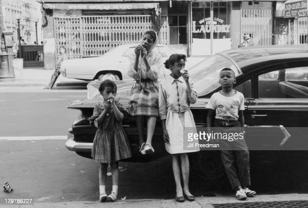 A group of children lean against a car to eat candy New York City 1966