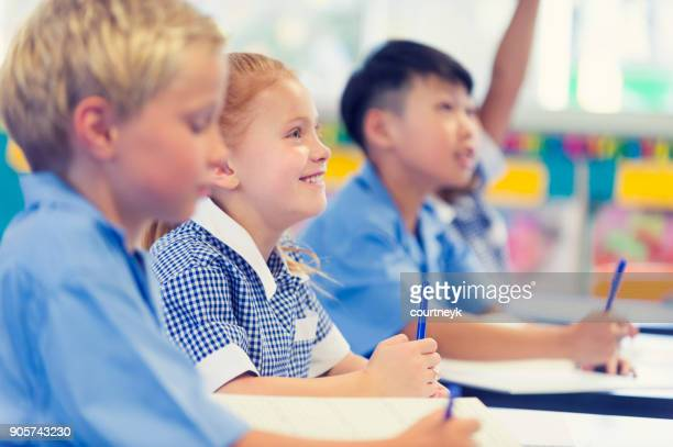 group of children listening to the teacher. - classroom stock photos and pictures