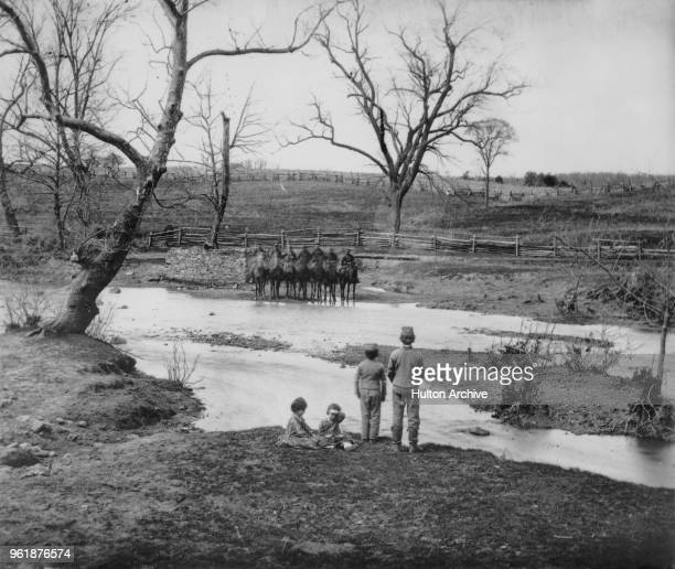 A group of children look on as a troop of cavalry from the Union Army of the Potomac water their horses in the stream on the old battlefield of Bull...
