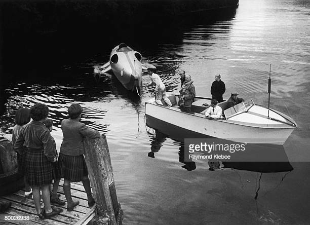 A group of children look on as British racing driver John Cobb brings his jet powered speed boat 'Crusader' back to the shore of Loch Ness Scotland...