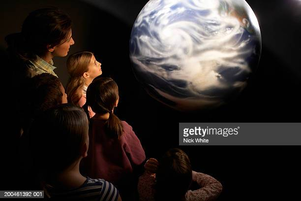 Group of children (8-10) looking at model of Earth