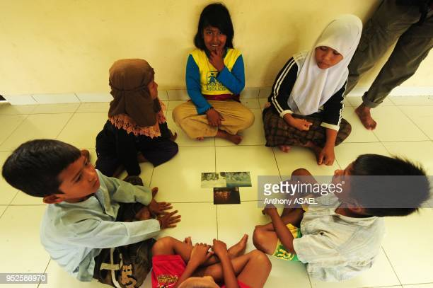 group of children looking at photographs during Art in All of Us activities Banda Aceh Sumatra Indonesia