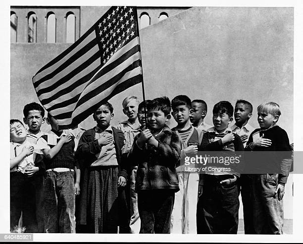 A group of children of mixed ethnicities including those of Japanese descent say the Pledge of Allegiance while holding an American Flag just days...
