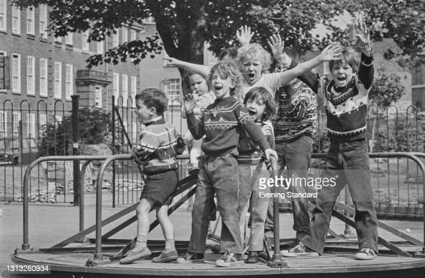 Group of children on a roundabout in a playground in Islington, London, UK, 9th June 1973.