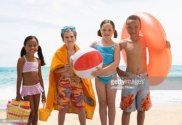 Group of children (6-9) on beach with holding various beach items, smiling, portrait