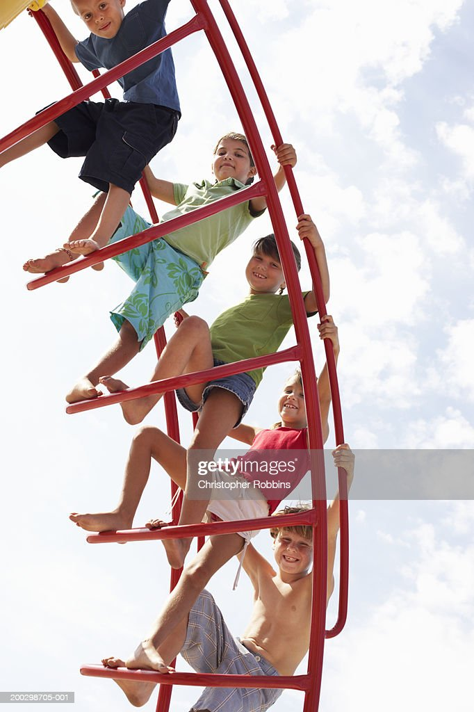 Group of children (6-9) on climbing frame, portrait, low angle view : Stock Photo