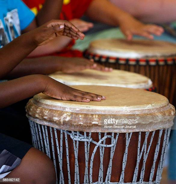 A group of children participating in a program with Akron Public Schools' Project RISE play djembe drums under the instruction of drum master Baba...