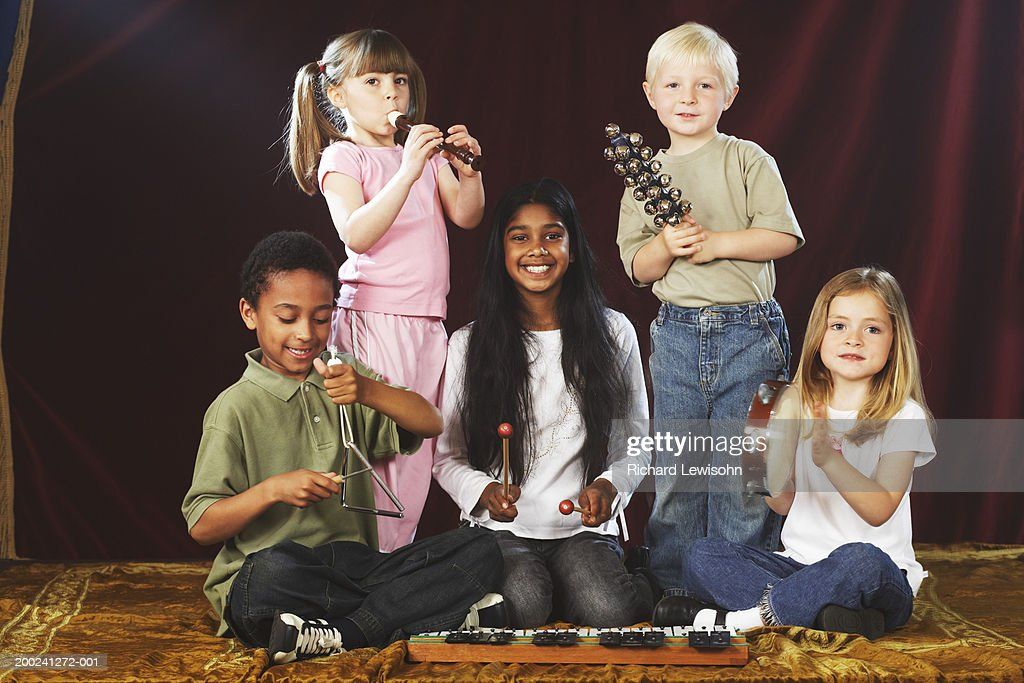 Group of children (4-9) performing on stage with musical instruments, portrait : Stock Photo
