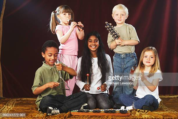 Group of children (4-9) performing on stage with musical instruments, portrait