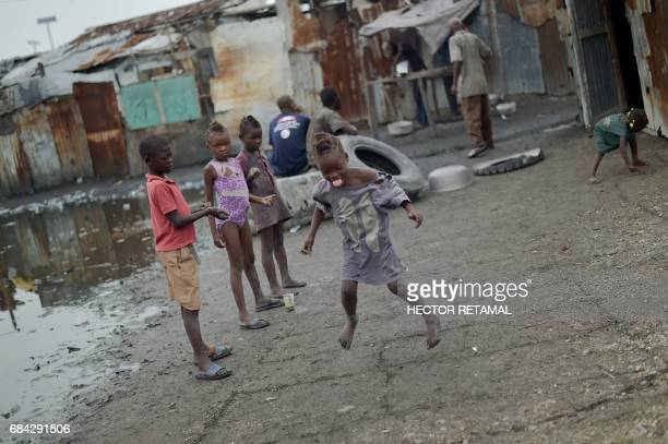 A group of children play in the neighborhood of Cite Soleil in PortauPrince on May 17 2017 / AFP PHOTO / HECTOR RETAMAL