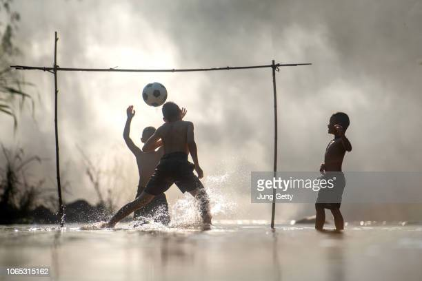 group of children playing a football on nature river at thailand - club football foto e immagini stock