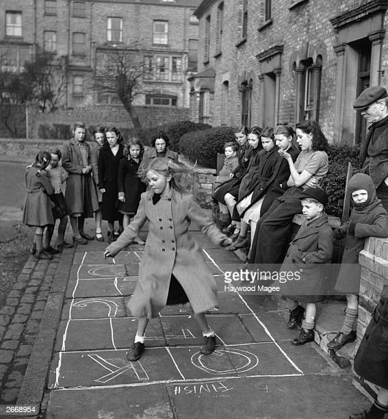 A group of children playing a game of hopscotch in a London street April 1950 Original Publication Picture Post 5005 Children's Street Games pub 1950