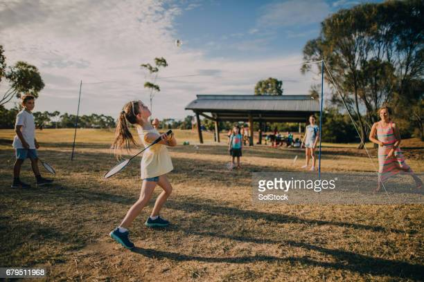 group of children playing badminton in the park - badminton stock photos and pictures