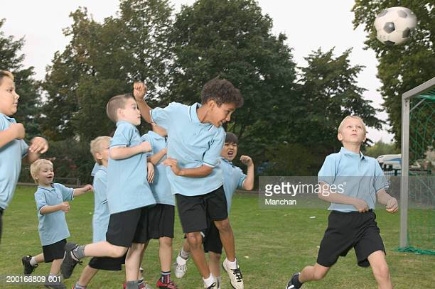 group of children (5-9) playing football - heading the ball stock pictures, royalty-free photos & images