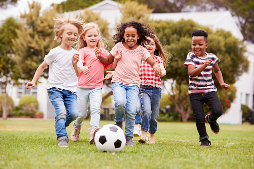 Group Of Children Playing Football With Friends In Park 1160929154