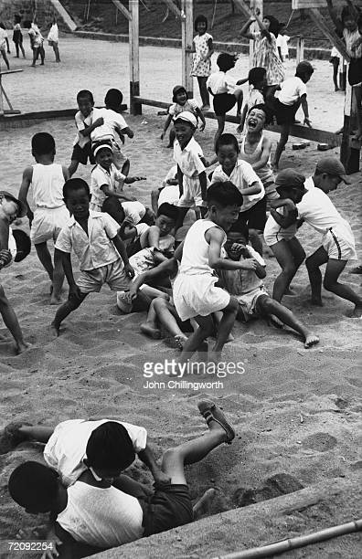 Group of children playing in a sandpit in Hiroshima, ten years after an atomic bomb was dropped on the city, 6th August 1955. Original Publication :...