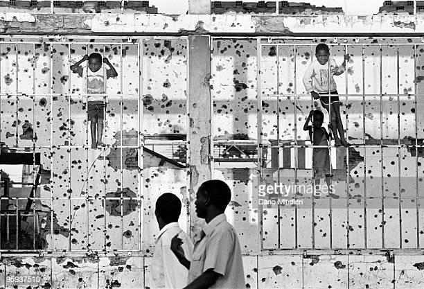 A group of children playing in front of a devastated bullet ridden wall in Kuito Angola in 1997 The town was the scene of the fiercest battles...