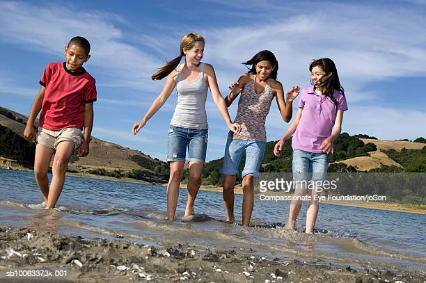 group of children (11-14 years) playing in lake, low section - 14 15 years stock pictures, royalty-free photos & images