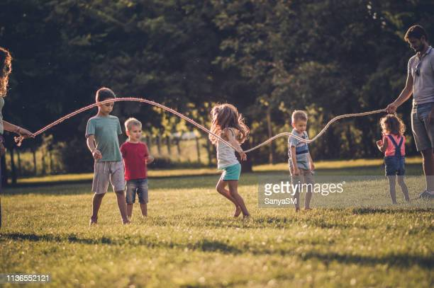 group of children playing in public park - skipping along stock pictures, royalty-free photos & images