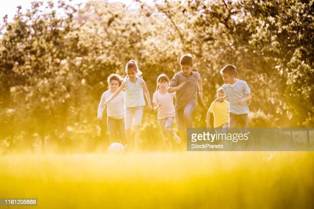 gruppo di bambini che giocano nel parco pubblico - club football foto e immagini stock