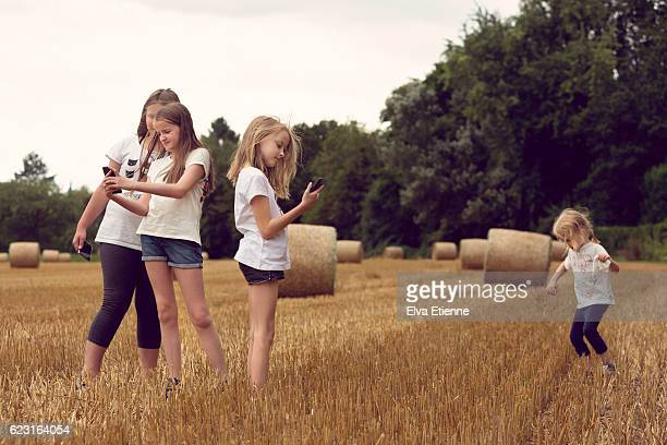 Group of children playing on phones outdoors