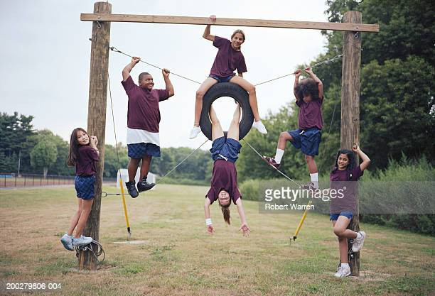 Group of children (9-12) playing outdoors, smiling