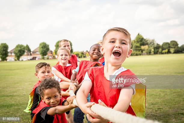 group of children playing tug of war - contest stock pictures, royalty-free photos & images