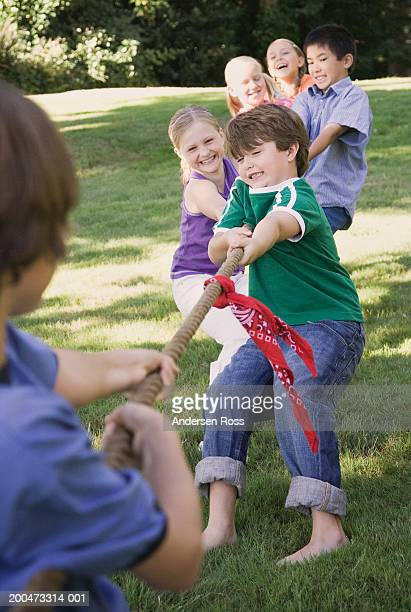 Group of children (7-12) playing tug-of-war