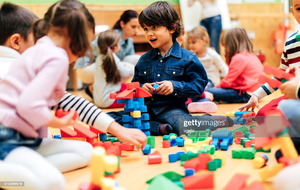 Group of children playing with blocks in kindergarten. : Stock Photo