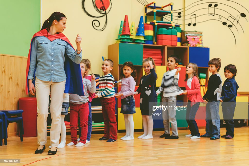 Group of children playing with their teacher in kindergarten : Stock Photo