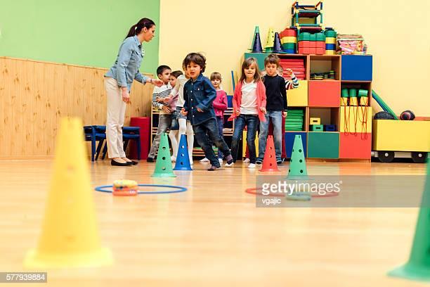 Group Of Children Playing With Their Teacher In Kindergarten