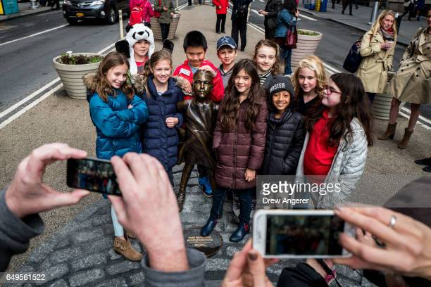 A group of children pose for a photo with 'The Fearless Girl' statue across from the iconic Wall Street charging bull statue March 8 2017 in New York...