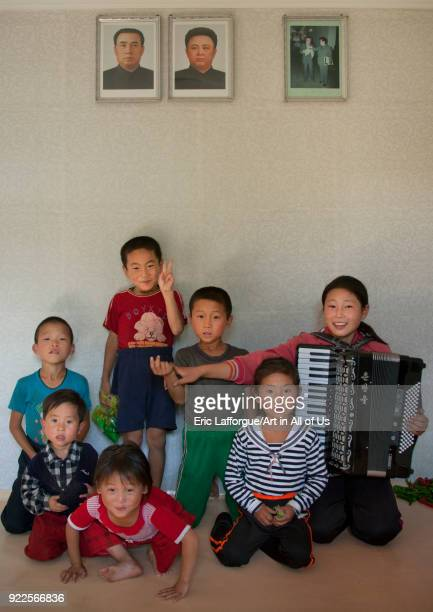 Group of children posing under Kim Jong il and Kim il Sung portraits in a house South Pyongan Province Chonsam Cooperative Farm North Korea on...