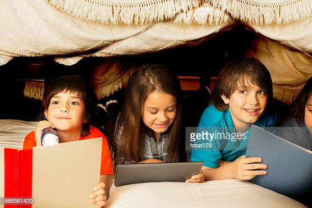 group of children read together in homemade tent at home. - fort stock pictures, royalty-free photos & images