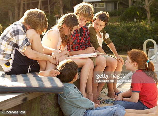 Group of children (7-13) reading, outdoors