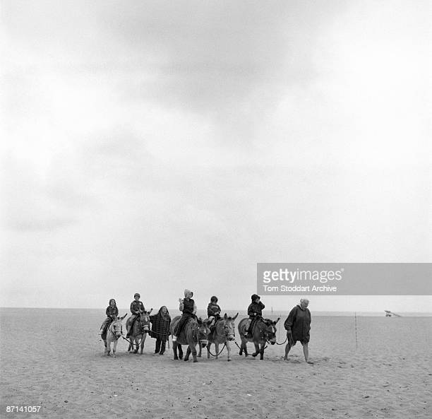 Group of children riding donkeys on the beach at Great Yarmouth, Norfolk, May 2007.